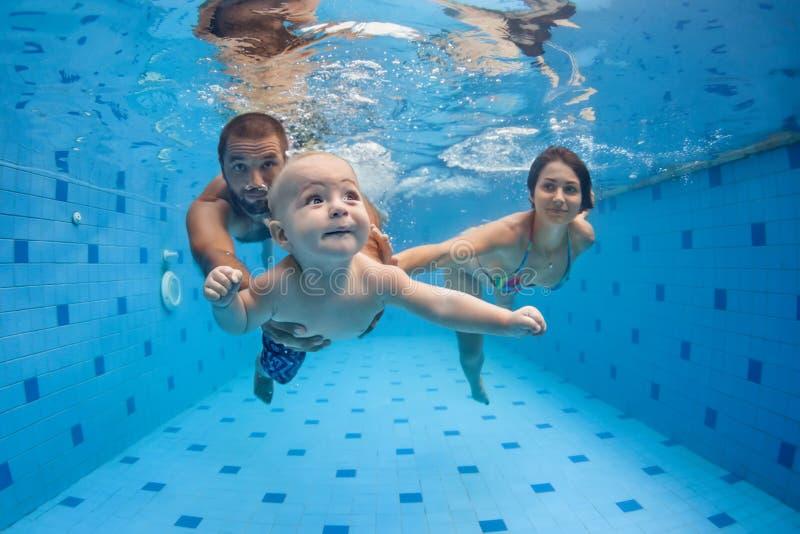 Glückliches volles Familienschwimmen und -tauchen Unterwasser im Swimmingpool stockfotos
