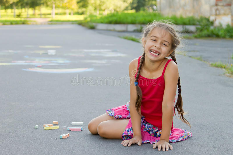 Glückliches Vorschulmädchen mit Kreiden auf der Pflasterung glücklich sitzen lachend stockfotografie