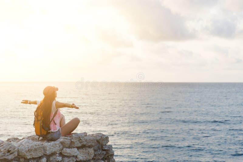 Glückliches Wanderermädchen, das auf Felsen sitzt und Meer betrachtet stockfotos
