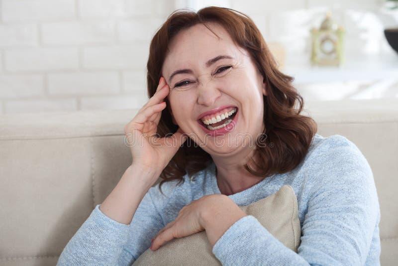 Glückliches weibliches Gesicht Attraktive und schöne mittlere Greisin, die auf Sofa sitzt stockbild