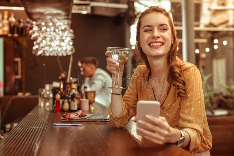 Glückliches weibliches haltenes Telefon und ein Martini-Cocktail in den Händen stockbild