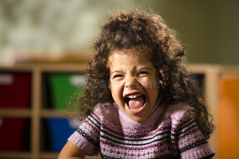 Glückliches weibliches Kind, das für Freude im Kindergarten lächelt stockfotos