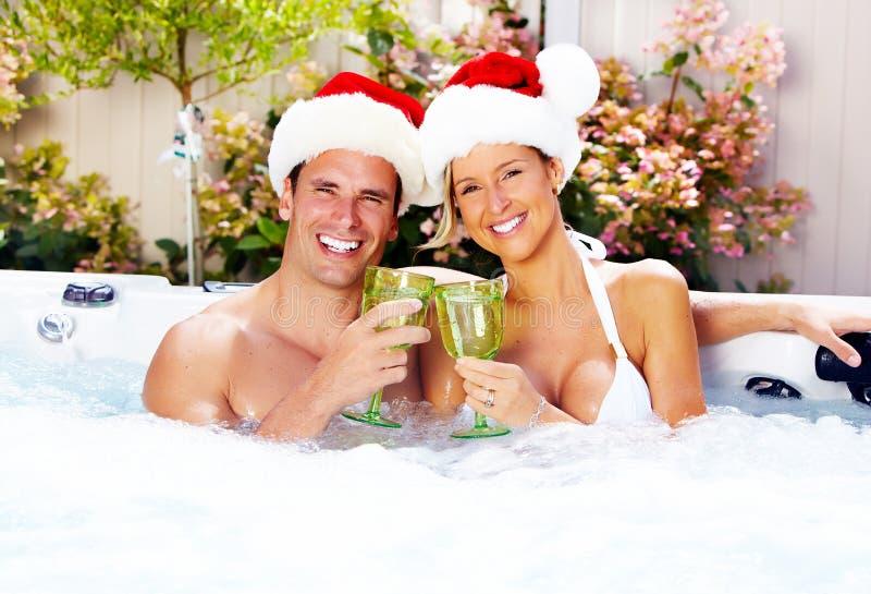 Glückliches Weihnachts-Sankt-Paare im Jacuzzi. stockfotos