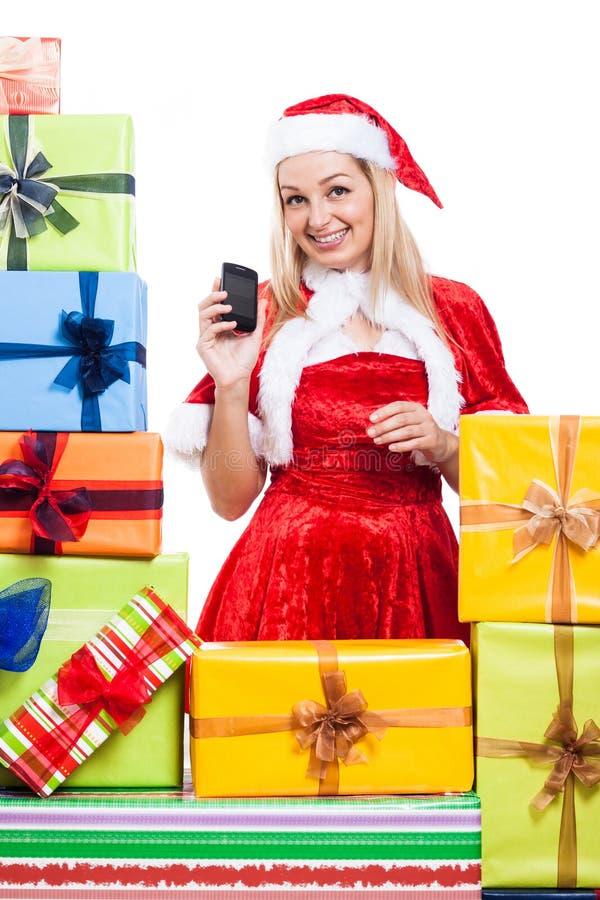 Glückliches Weihnachtsfrau mit Telefon und Geschenken lizenzfreie stockfotografie