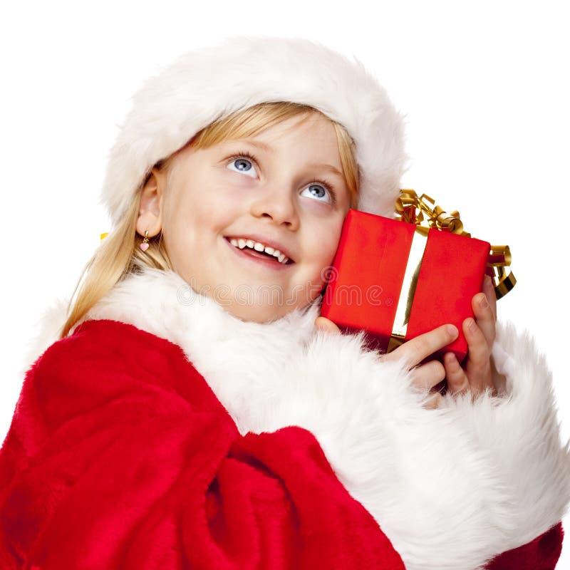 Glückliches Weihnachtsmann-Kind hält Weihnachtsgeschenk an stockfotos
