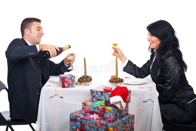 Glückliches Weihnachtspaare, die für Toast sich vorbereiten lizenzfreie stockfotografie