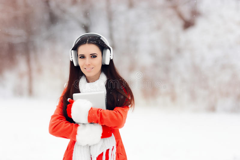 Glückliches Winter-Mädchen mit Kopfhörern und PC Tablet stockfotografie