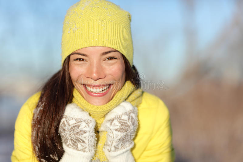 Glückliches Wintermädchen, das Spaß im Schnee habend lacht stockfoto