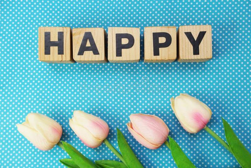 Glückliches Wort gemacht von den hölzernen Würfeln mit Buchstabealphabet stockfotos