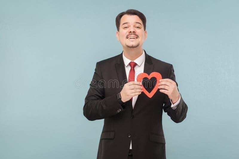 Glückmann, der kleines rotes Herz hält und Kamera betrachtet lizenzfreie stockfotografie