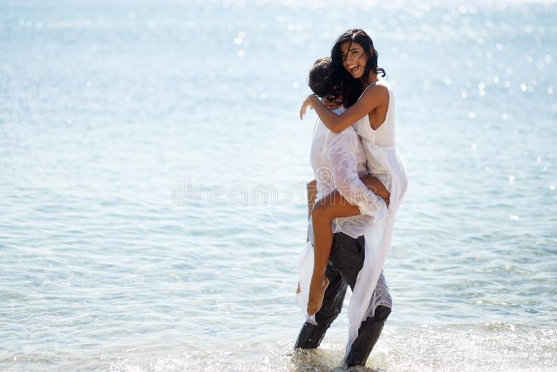 Glückpaare genießen auf dem Strand, das verlockende Bild von verrückten Jungvermählten, lokalisiert auf einem Mittelmeer des blau lizenzfreies stockfoto