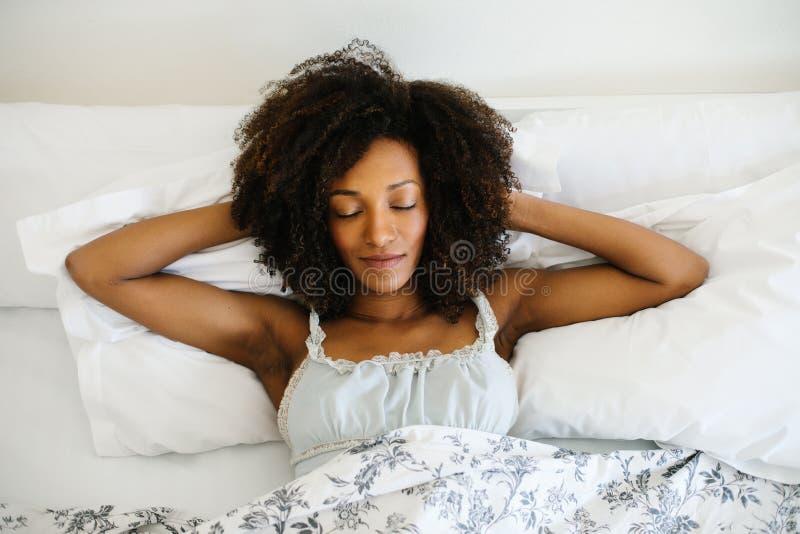 Glückselige Frau, die sich zu Hause in ihrem Bett entspannt stockfotografie