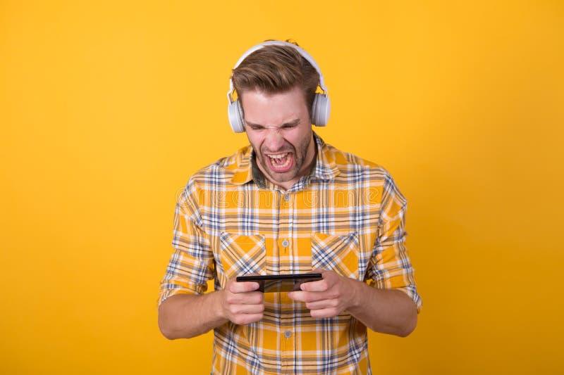 An Glücksspielen beteiligt Musikabonnement Mann zufrieden mit Musik, modernen Kopfhörern und Smartphones Beste Musikapplikationen stockfoto
