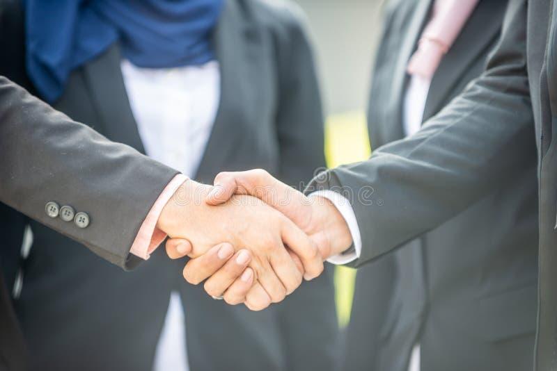 Glückwünsche! Moslemische asiatische Geschäftsleute rütteln Hand stockbilder