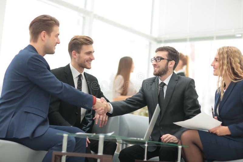 Glückwünsche! Zwei nette Geschäftsmänner, die Hände rütteln, während seien Sie lizenzfreies stockbild