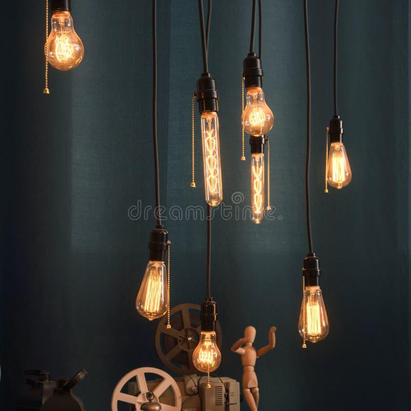 Glühbirnen auf blauem Hintergrund in der Dachbodenart stockbilder