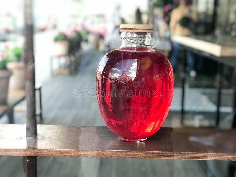 Glühende Bank des roten großen Glasdreiliters einer Haube, Saft, Tränke mit einem hölzernen Deckel auf einem unscharfen Hintergru lizenzfreie stockbilder