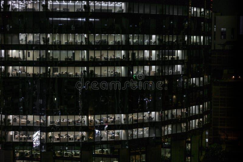 Glühende Fenster von Wolkenkratzern am Abend - Ansicht von modernen Büros in einem Gebäude lizenzfreie stockbilder