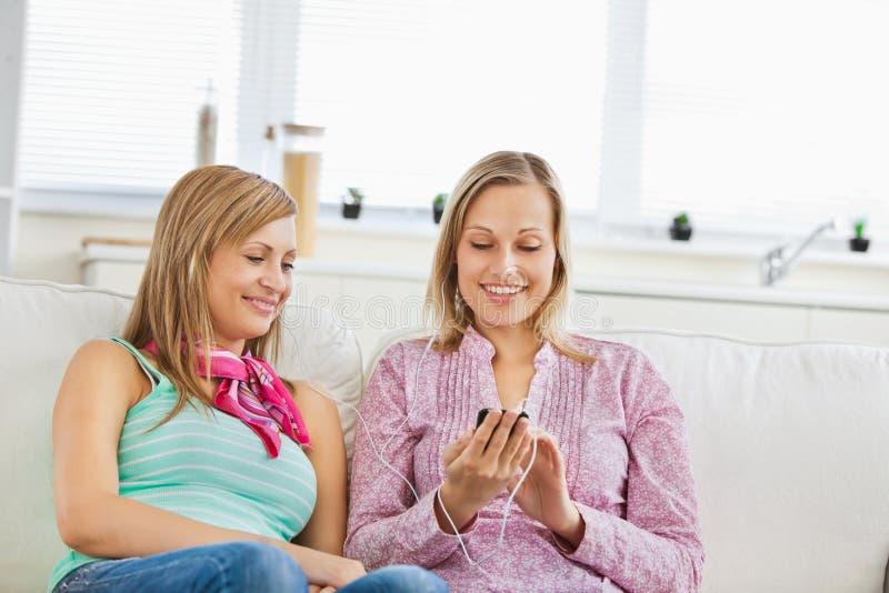 Glühende Freunde hören Musik unter Verwendung eines Mobiltelefons stockbild
