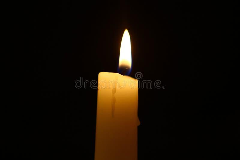 Glühende gelbe Kerze des kleinen Paraffins mit hellem Feuer auf dem schwarzen Hintergrund lizenzfreies stockbild