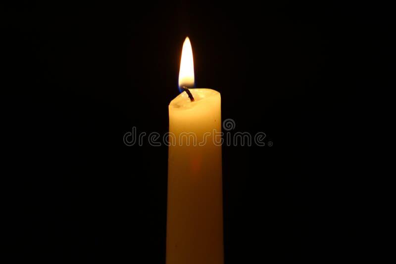 Glühende gelbe Kerze des kleinen Wachses mit klarem Feuer gegen den starken schwarzen Hintergrund stockfotos