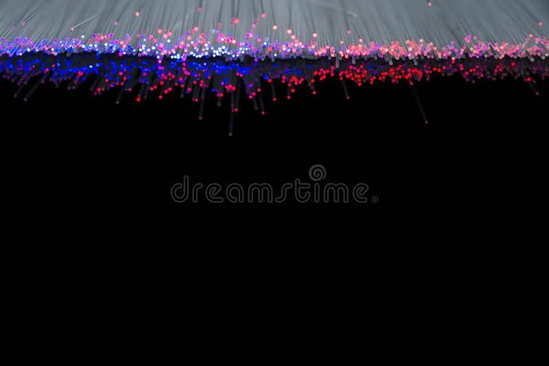 Glühende Glasfasern des blauen Rotes nah herauf Makroschuß auf dem Reflektieren der dunklen Oberfläche stockbild