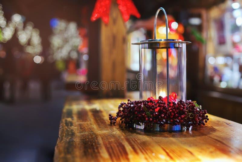 Glühende Kerzenlaterne auf dem Tisch am Weihnachtsmarkt am Abend Belichtet mit Licht stockfoto