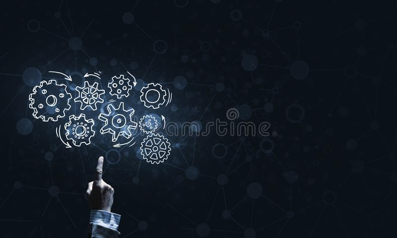 Glühende Zahnradmechanismusikone auf dunklem Hintergrund als Symbol der Teamwork lizenzfreies stockbild