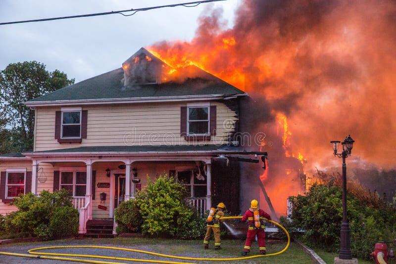 Glühender Hausbrand des Feuerwehrmannkampfes stockfotografie