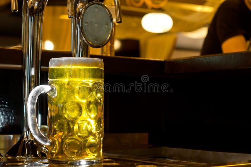 Glühender Krug des goldenen Fassbiers lizenzfreies stockfoto