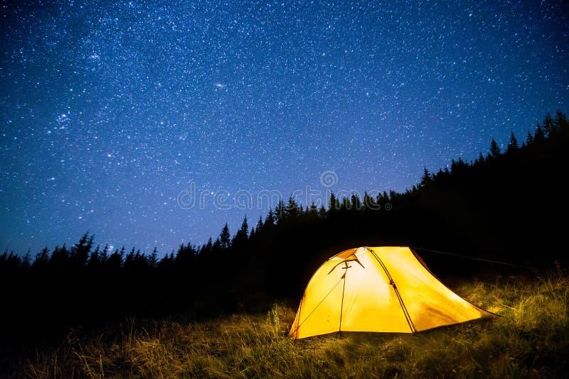 Glühendes Campingzelt im Nachtgebirgswald unter einem sternenklaren Himmel stockfotografie