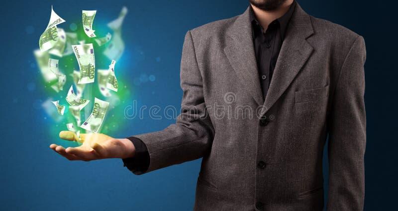Glühendes Geld in der Hand eines Geschäftsmannes stockbilder