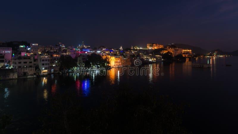 Glühendes Stadtbild bei Udaipur bis zum Nacht Die reflektierenden Lichter des majestätischen Stadtpalastes auf See Pichola, Reise stockfotografie