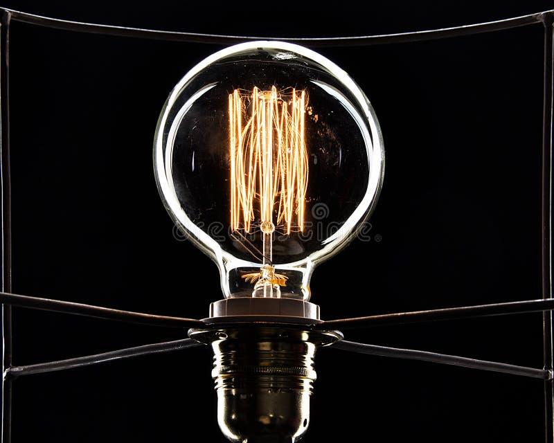 Glühlampe auf einem schwarzen Hintergrund Goldene Spirale stockbild