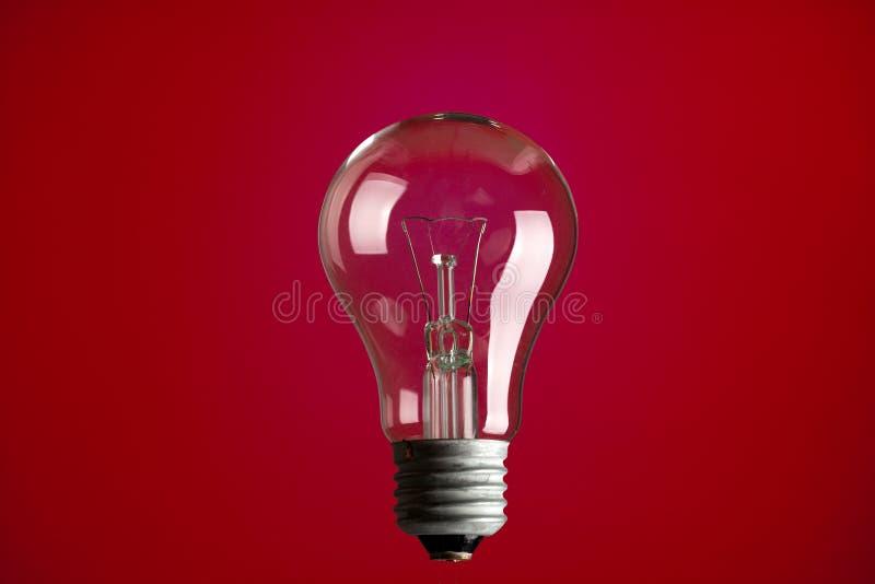 Glühlampe auf rotem Hintergrund stockfotografie