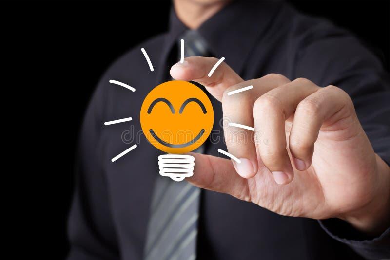 Glühlampe der Geschäftsmannhandshow mit Lächelnikone lizenzfreies stockbild