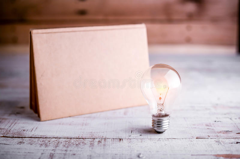 Glühlampe und leerer Kalender stockfotografie