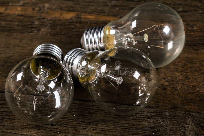 Glühlampen auf hölzernem Hintergrund lizenzfreie stockbilder