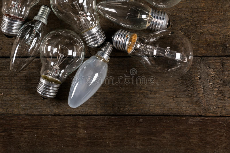 Glühlampen auf hölzernem Hintergrund stockfotografie