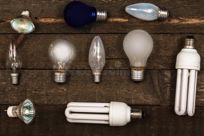Glühlampen auf hölzernem Hintergrund lizenzfreie stockfotos