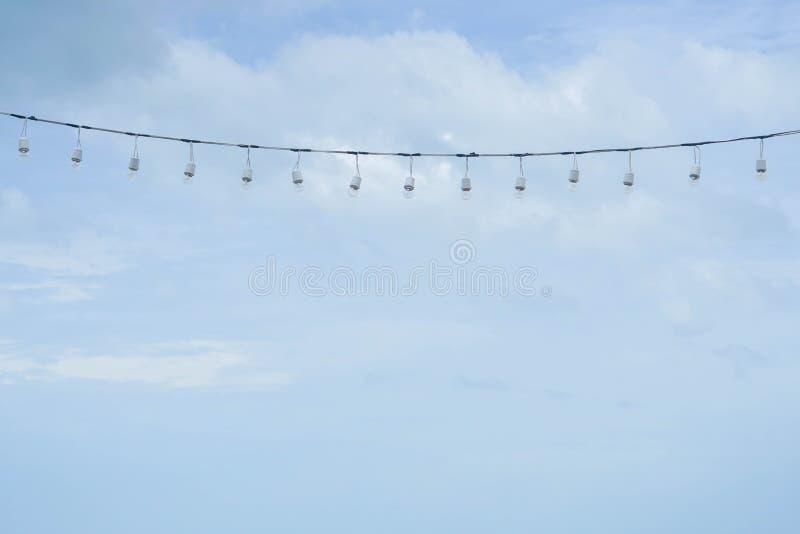 Glühlampen der Weinlese, die im blauen Himmel hängen stockbild
