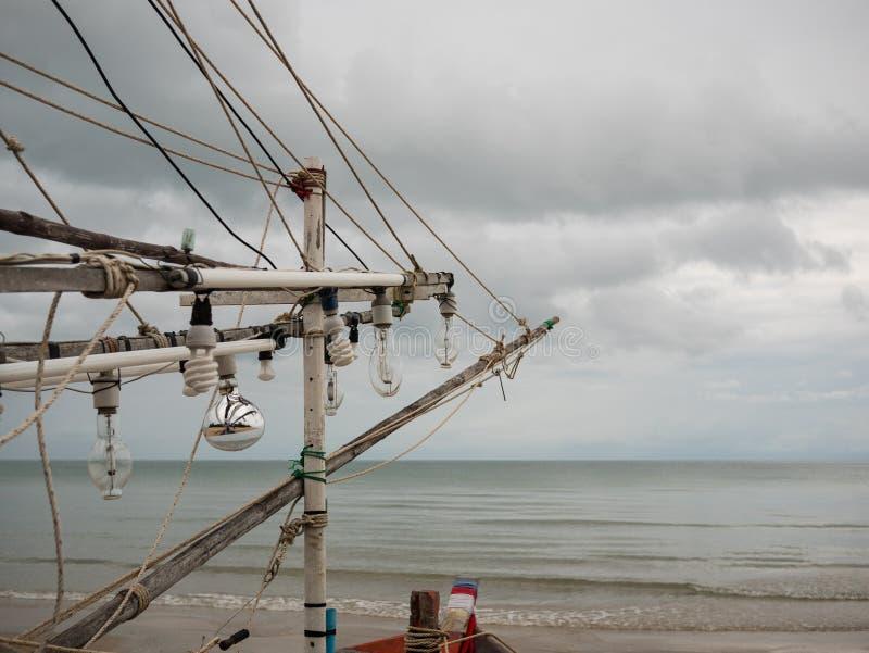 Glühlampen des Fischerbootes des Kalmars auf dem Strand am bewölkten Morgentag lizenzfreies stockfoto