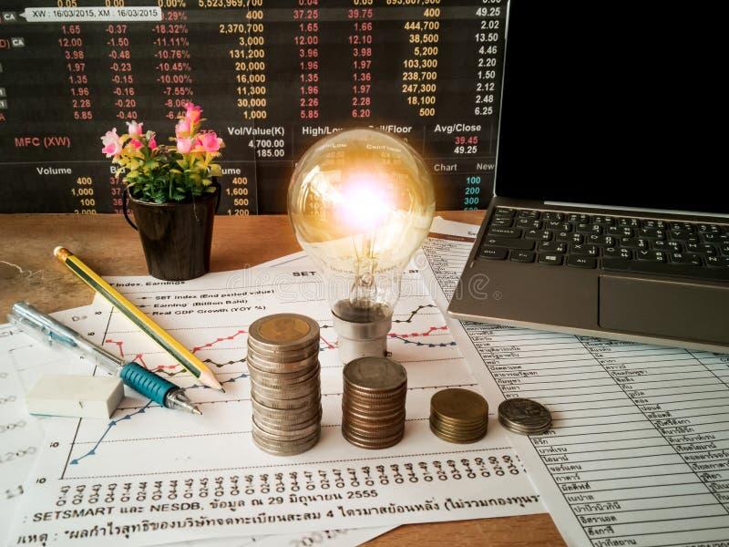 Glühlampen werden in Geschäftsunterlagen und in Finanzbuchhaltungskonzepte gelegt stockfotos