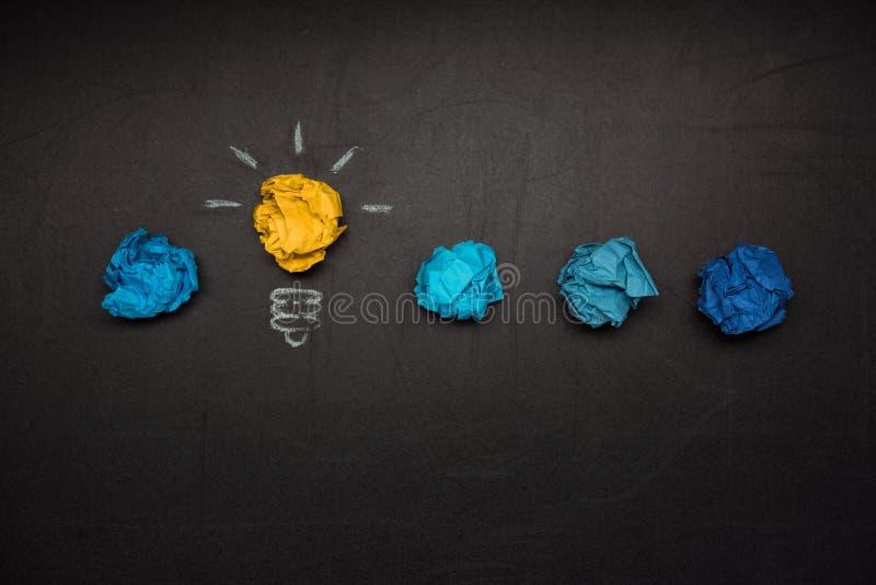 Glühlampesymbol und zerknitterte Papiere nahe vorbei auf Tafel stockfotografie