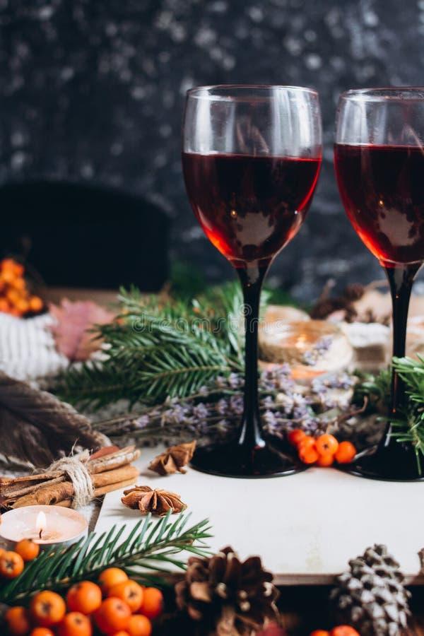 Glühwein in den Gläsern, in den roten Beeren, in den Stößen und im Herbst verzweigt sich auf Holztisch lizenzfreies stockfoto