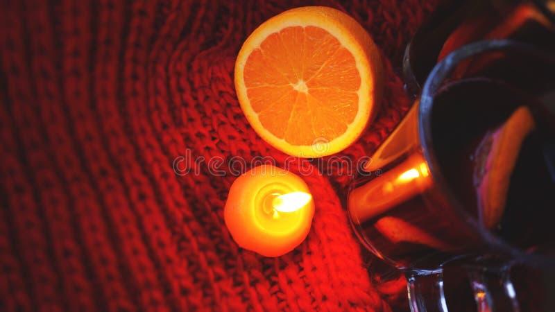 Glühwein in den Glasbechern, brennende Kerze auf einem dunkelroten Hintergrund Glühender Wein stockfotos