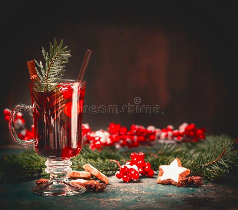 Glühwein im Glasbecher mit Wintergewürzen auf Tabelle am dunklen Hintergrund lizenzfreies stockfoto