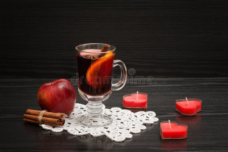 Glühwein mit Gewürzen auf einer Spitzeserviette Kerzen in der Form O stockfoto