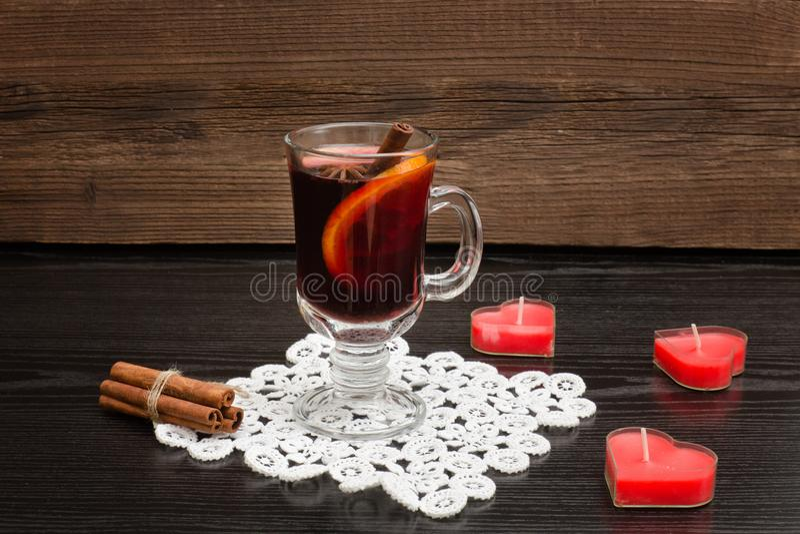 Glühwein mit Gewürzen auf einer Spitzeserviette Kerzen in der Form O lizenzfreies stockbild