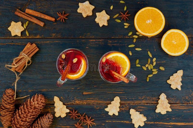 Glühwein mit orange Scheiben und heißen Wintergewürzen - Zimt-, Kardamom- und Anissterne auf dem schwarzen hölzernen Hintergrund lizenzfreie stockfotos